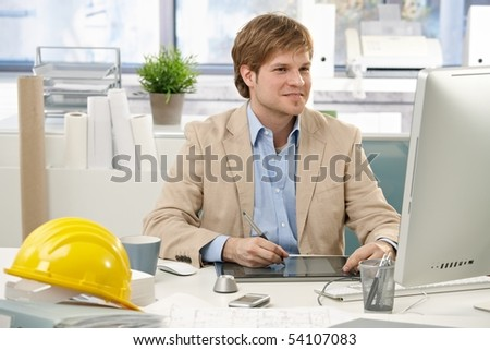 Young architect sitting at office desk, drawing pad, looking at screen. - stock photo