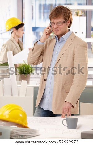 Young architect standing at office desk, talking on mobile phone. - stock photo