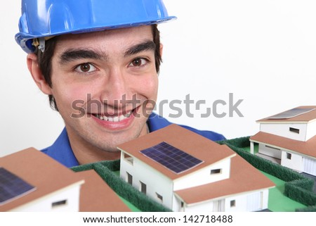 Young architect stood by model housing - stock photo