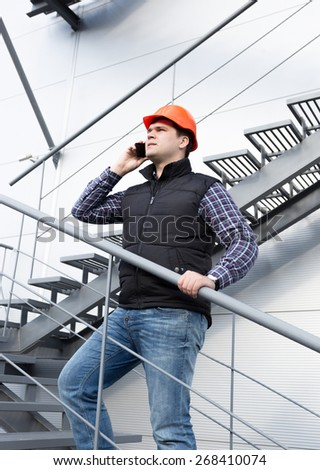 Young architect talking on phone while inspecting factory - stock photo