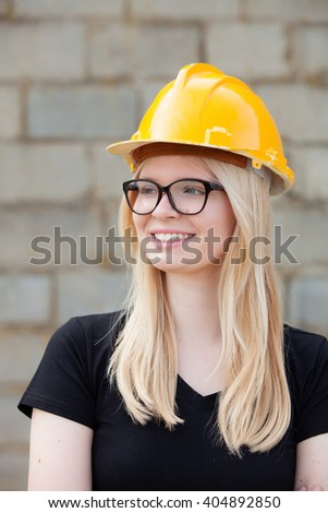 Young architect with yellow helmet near his workplace - stock photo