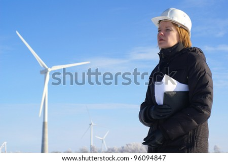 Young architect-woman wearing winter cloth standing against wind turbines - stock photo