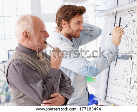 Young architect working together at drawing board being supervised by senior. - stock photo