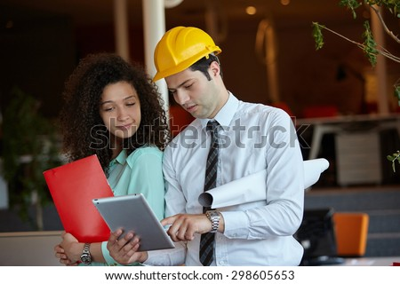 Young Architects in office looking at construction project