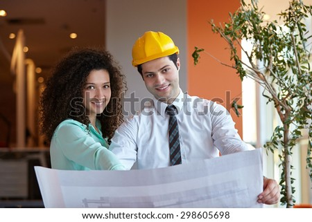 Young Architects in office looking at construction project - stock photo