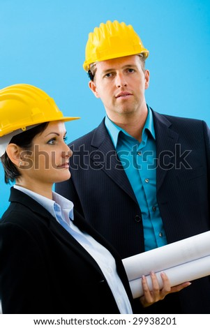Young architects in yellow hardhat against blue background.
