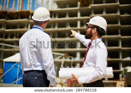 Young architects looking at construction and discussing its details - stock photo