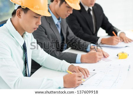 Young architects sitting in a row and drawing blueprints - stock photo