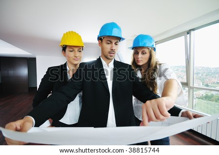 young arhitect group in big bright modern new apartment looking blueprints and building plans - stock photo