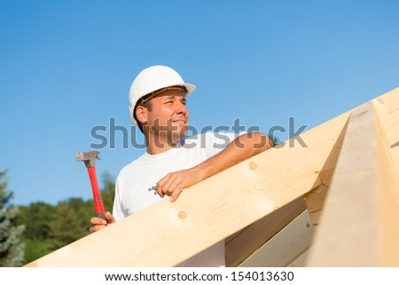 Young artisan working hard to build the roof of a new house - stock photo