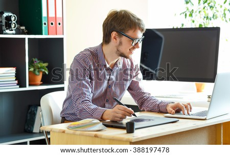 Young artist drawing something on graphic tablet at the home office - stock photo