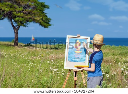 Young artist finishing his work, outdoor - stock photo