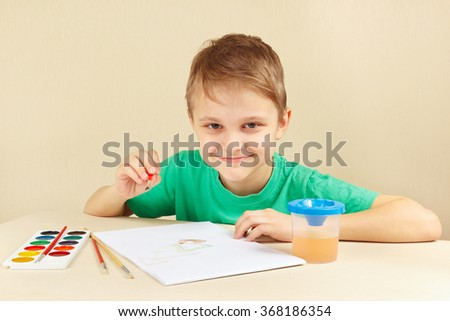 Young artist in a green shirt painting with watercolors - stock photo