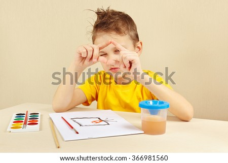Young artist in a yellow shirt painting colors from nature - stock photo