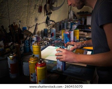 Young artist in his studio workng on spray paint art. - stock photo