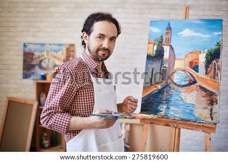 Young artist looking at camera on background of his painting - stock photo