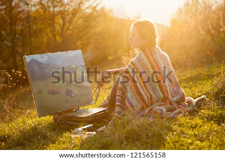 Young artist painting an autumn landscape - stock photo