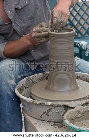 Young artist shaping a clay pot with hands.
