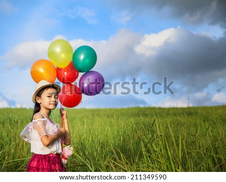 young asia girl holds tightly to a large bunch of helium filled balloons in nature park - stock photo