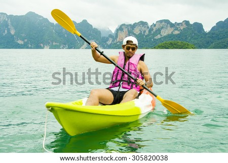 Young Asia man paddling in Chiewlarn dam in Surat Thani, Thailand