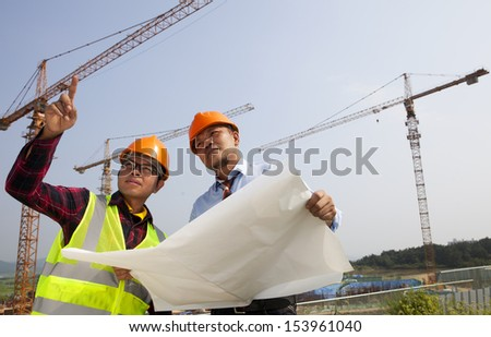 Young asian architects discussion at blueprint in front of construction site, horizontal image - stock photo