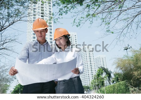 Young Asian architects standing outdoors with construction plan - stock photo