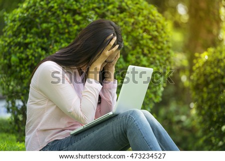 Young asian beautiful woman is feeling stress, working on notebook/laptop outdoor, thinking about work load, sitting in a park