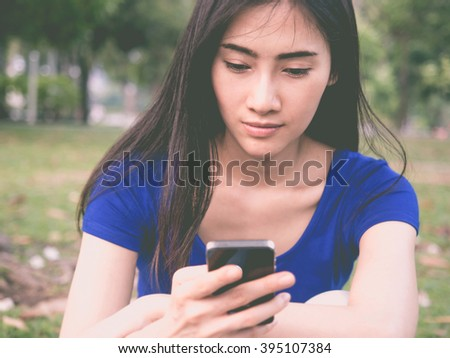 Young Asian beautiful woman reading message on mobile phone in the park, selective and soft focus with vintage tone (communication concept)
