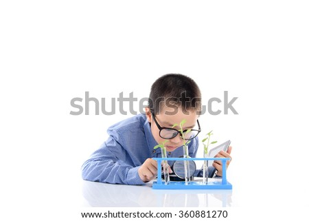 Young Asian boy check young seedling plant in glass tube for his experimental. carry tablet device on white background