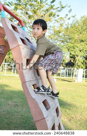 Young asian boy climbing on playground - stock photo