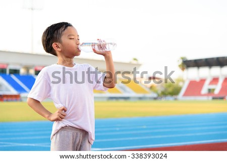 Young Asian boy drinking fresh water from plastic bottle after sport in stadium.