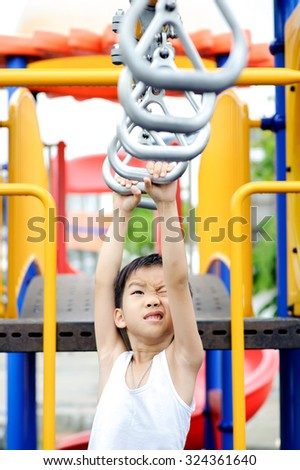 Young asian boy hang the metal bar by his hand to exercise at out door playground