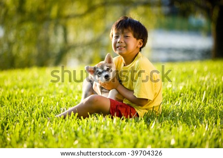 Young Asian boy holding Alaskan Klee Kai puppy sitting on grass - stock photo