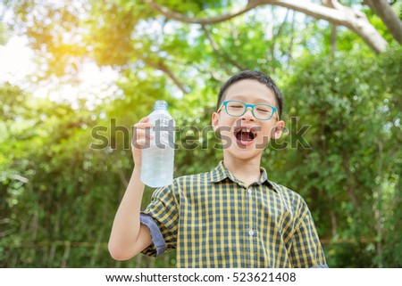 Young asian boy holding drink water bottle in park