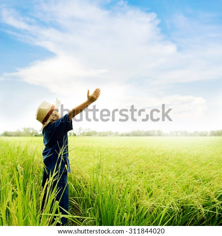 Young Asian boy in thai traditional blue shirt and straw hat feeling relax on the rice field be fore harvesting.