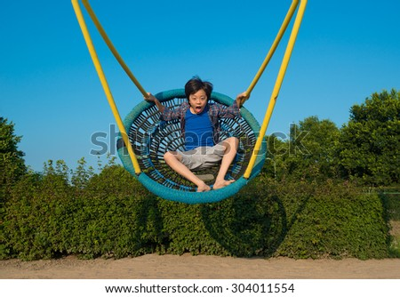 Young Asian boy on the swing - stock photo