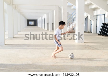 Young Asian boy play football alone in the empty white building.