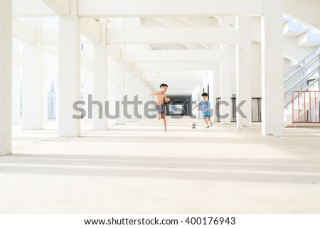 Young Asian boy play football in the empty white building.