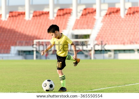 Young Asian boy play on the grass football field in the stadium during summer. - stock photo