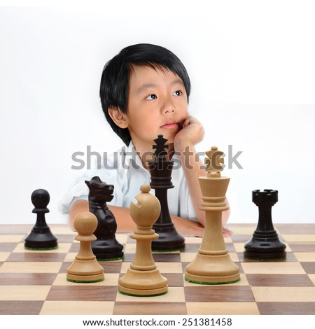 Young Asian boy playing chess - stock photo