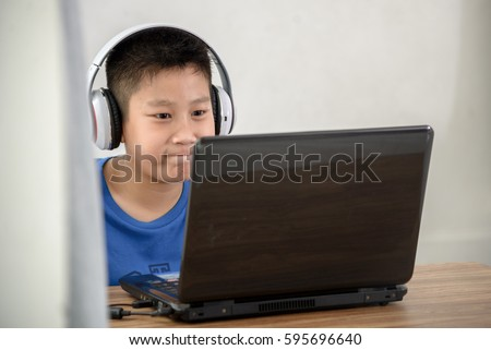 Young Asian boy playing game with laptop technology at home.