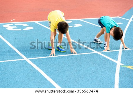 Young Asian boy prepare to start running on blue track in the stadium during day time to practice himself. - stock photo