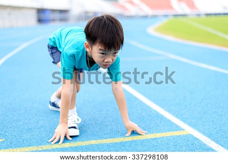 Young Asian boy prepare to start running on blue track in the stadium during day time to practice himself.