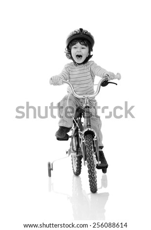 young asian boy riding on a tricycle on isolated background
