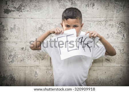Young Asian boy selecting post it notes describing his emotions - stock photo