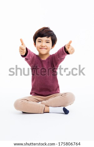 Young Asian boy showing thumb isoalte on white background.  - stock photo
