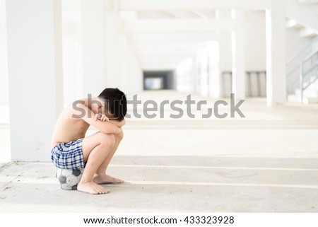 Young Asian boy sit on the old football alone in the white building. - stock photo