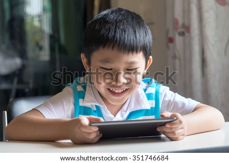 Young asian boy sitting , he browses the internet on a tablet computer at home - stock photo