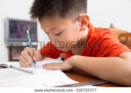 Young asian boy sitting on wood furniture doing homework