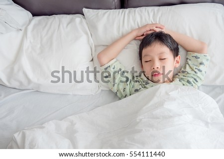 Young asian boy sleeping on bed in morning